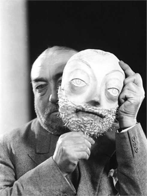 00/00/1935. The fashion designer Paul POIRET behind a bearded mask at his effigy, around 1935. Vers 1935, le couturier Paul POIRET derrière un masque barbu à son effigie.